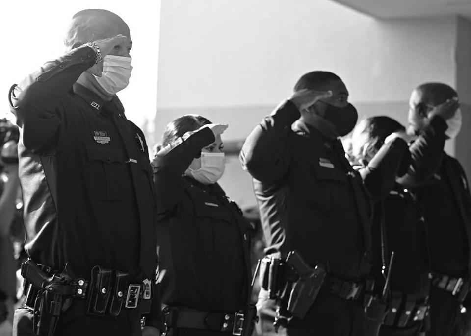 Police officers wearing masks salute