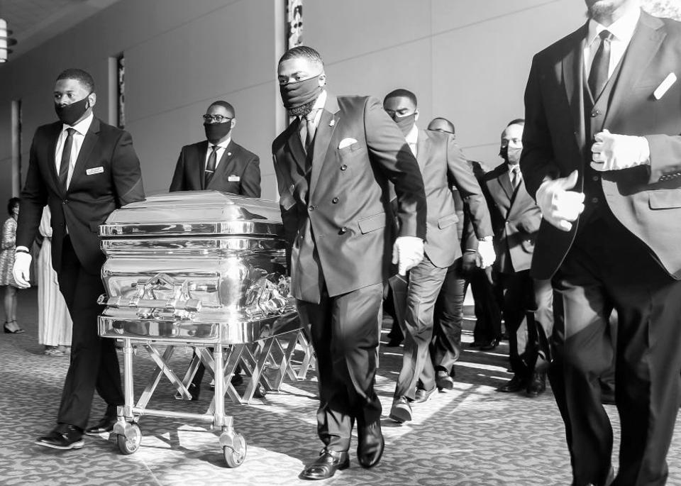 Men in suits and face masks pull a coffin