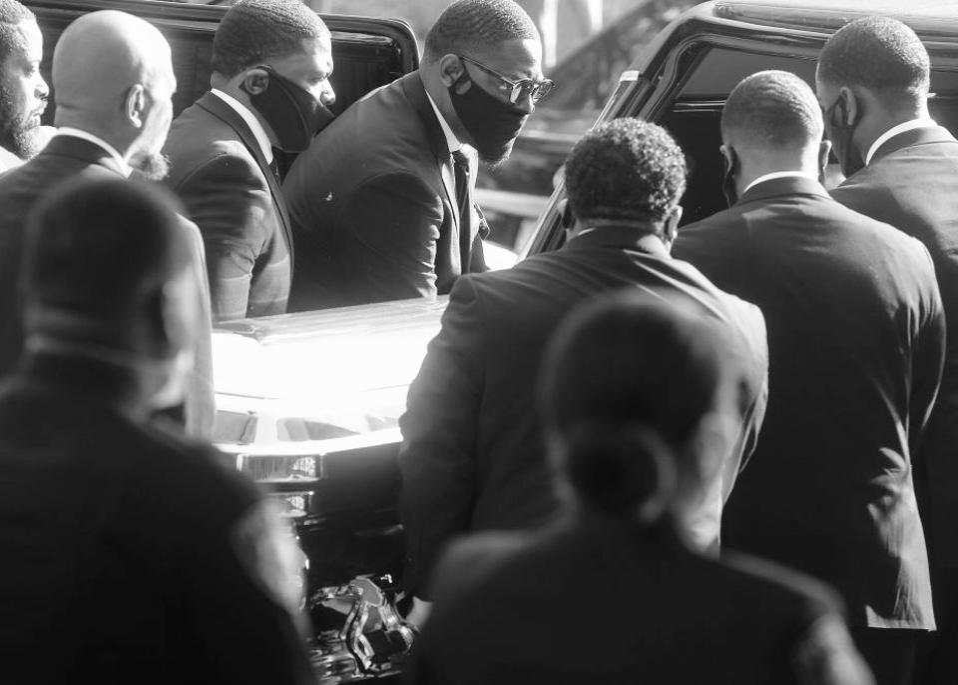 A crowd surrounds a coffin.