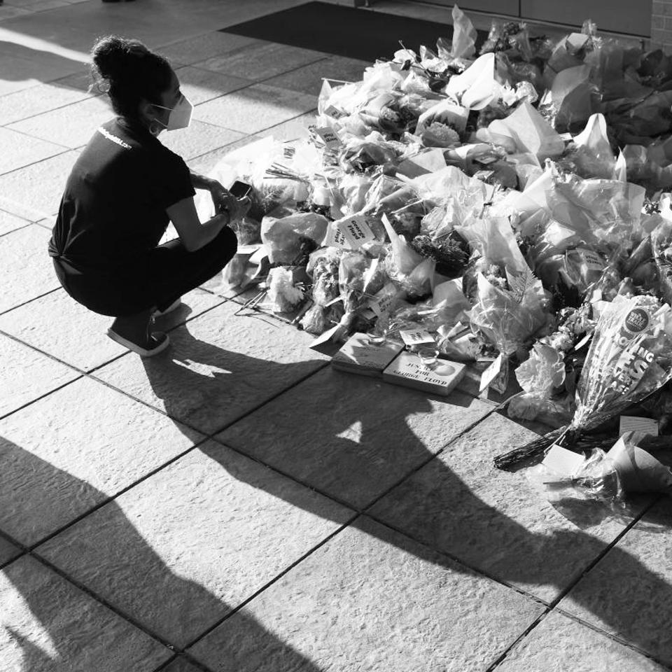A woman in a face mask kneels before flowers.
