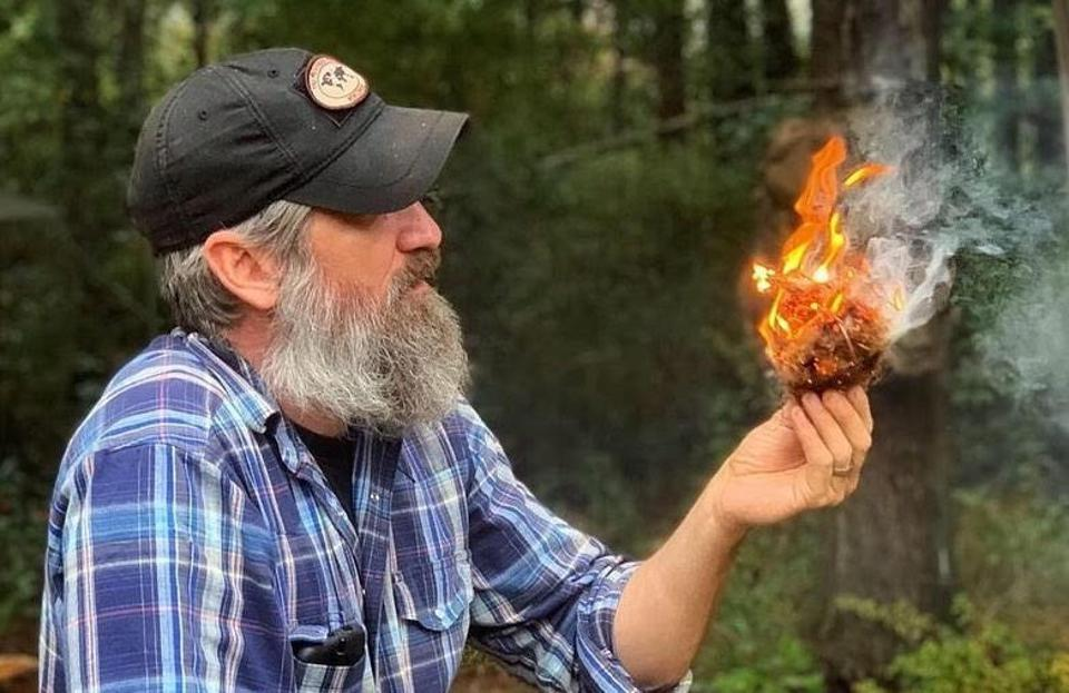 Man outdoors making a fire