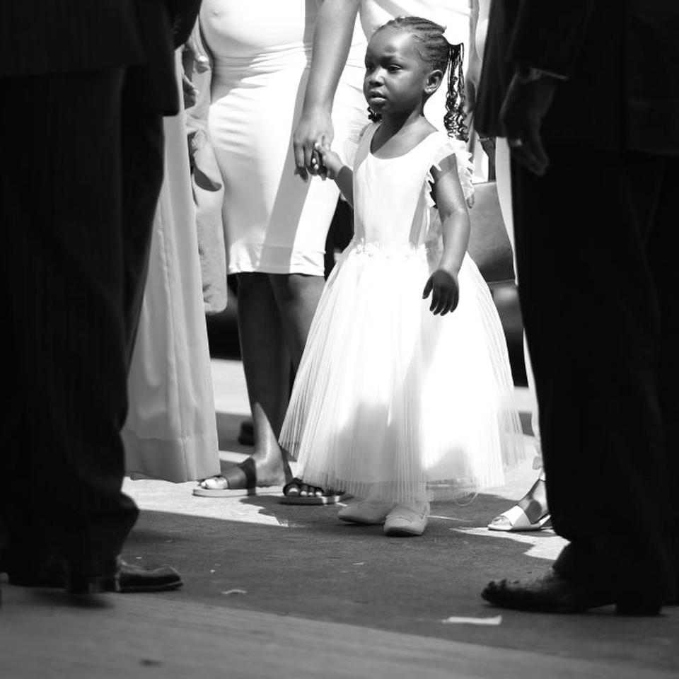 A little girl in a white dress enters the church holding an adult woman's hand.