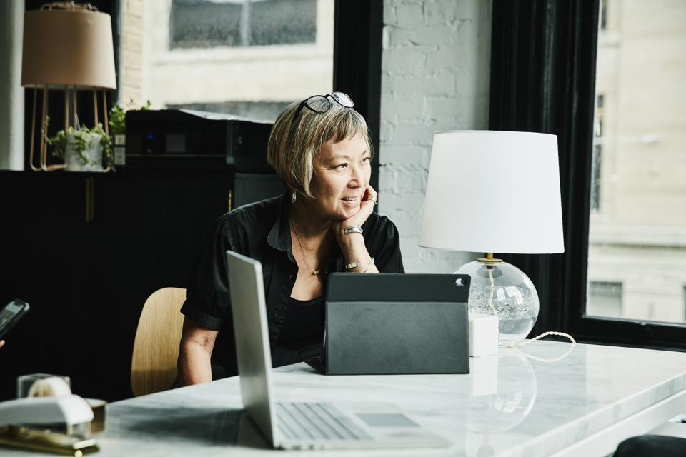 Portrait of smiling businesswoman seated at desk in creative office