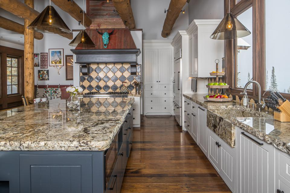 The kitchen features Sub-Zero appliances, custom cabinetry, a massive center island, and plenty of casual seating.