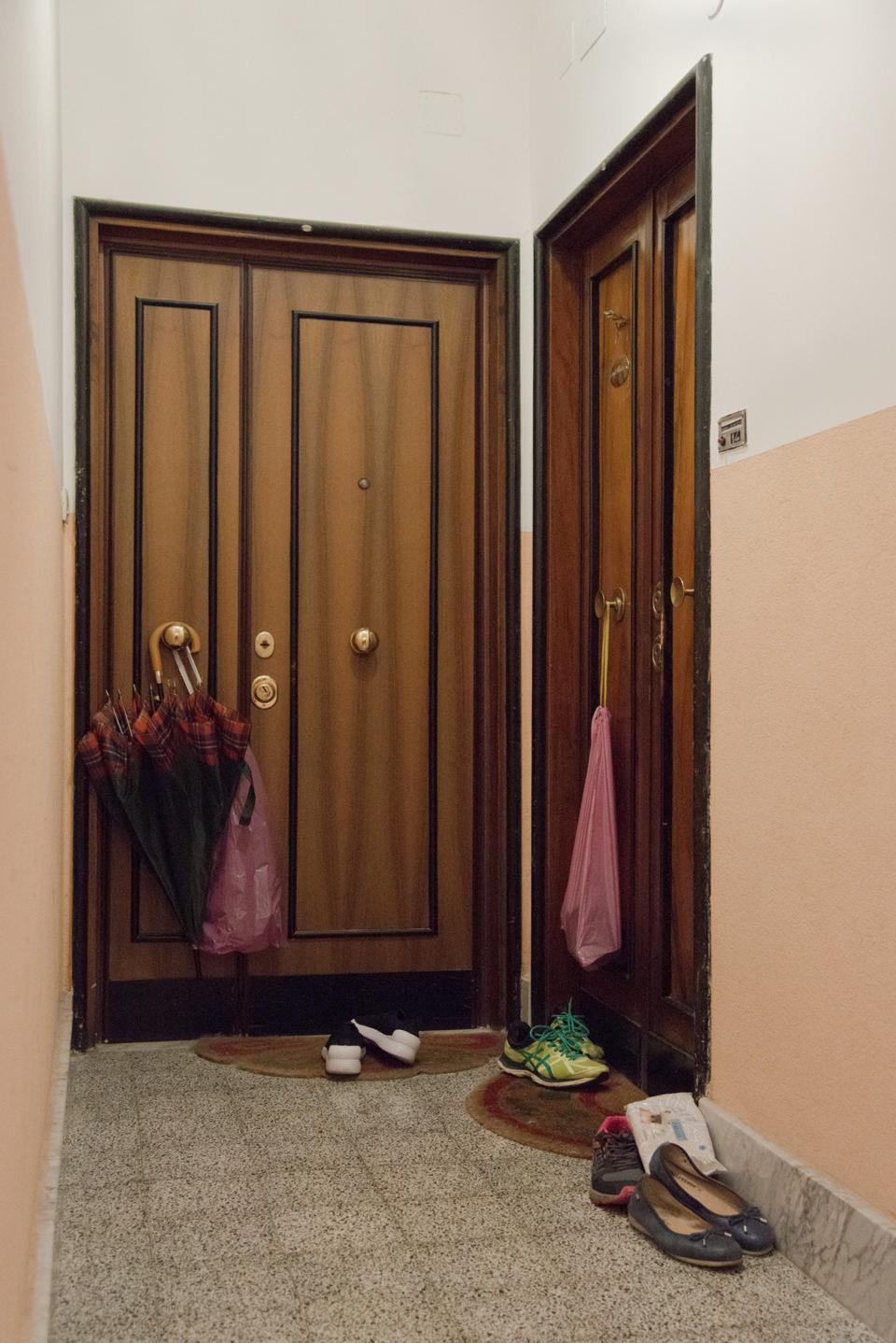 Shoes and shopping bags hang on doorways in an apartment building in Rome.
