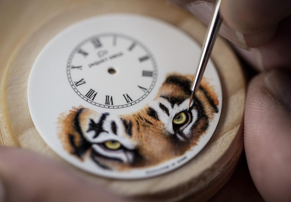 An artisan brings the tiger to life on a white Grand Feu enamel dial using a delicate brush.