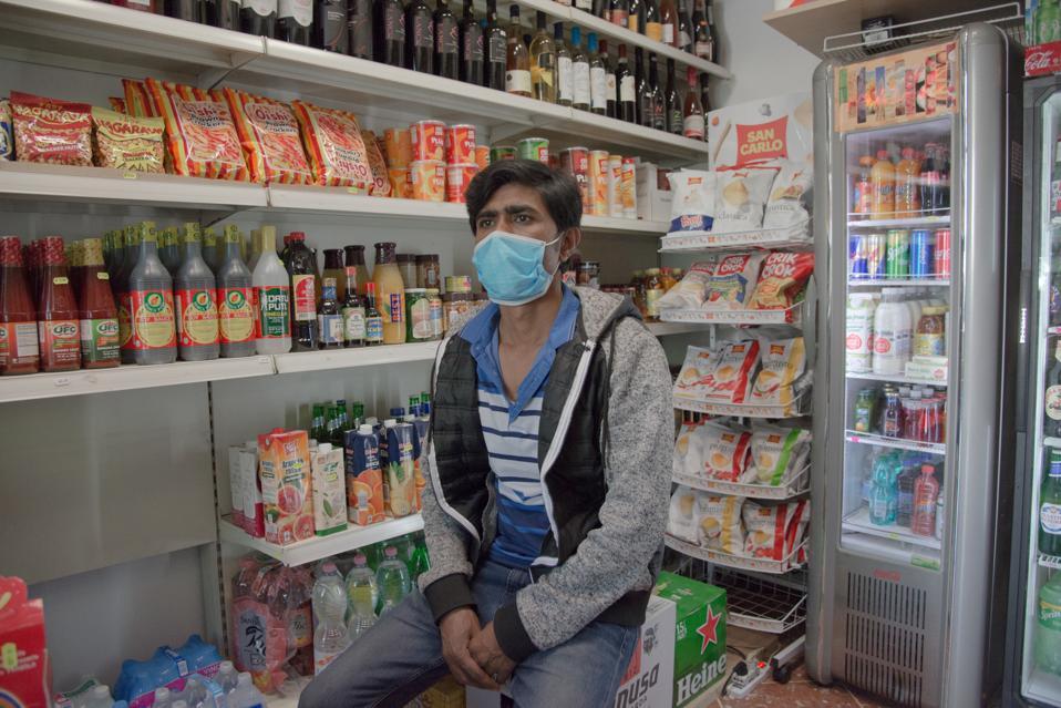 A man in a mask sits in a corner store in Rome.