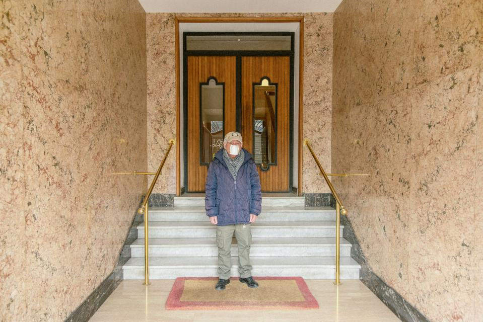 An elderly man wears a face mask in the entryway to a building in Rome.