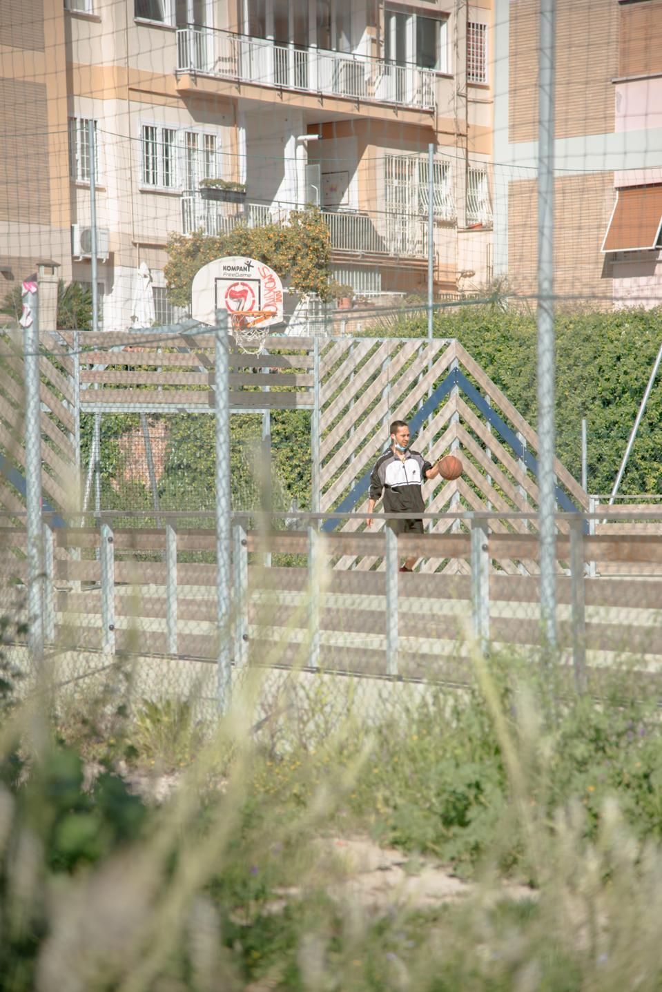 A man plays basketball in post-quarantine Rome.