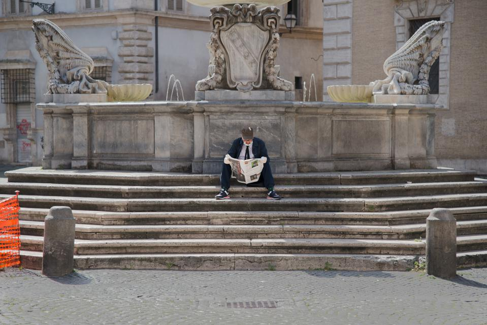 A man reads the newspaper in Rome.
