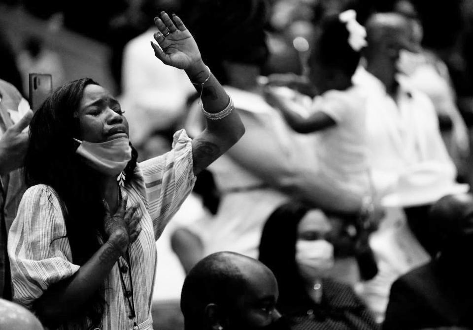 A woman holds her hand up and cries