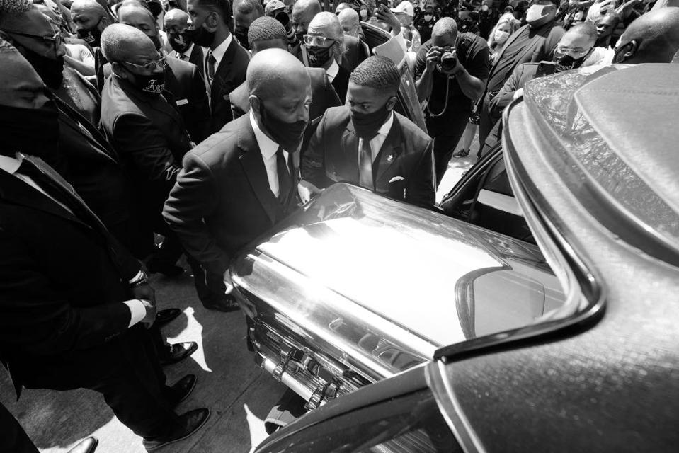 Men wearing face masks push a casket into a hearse.