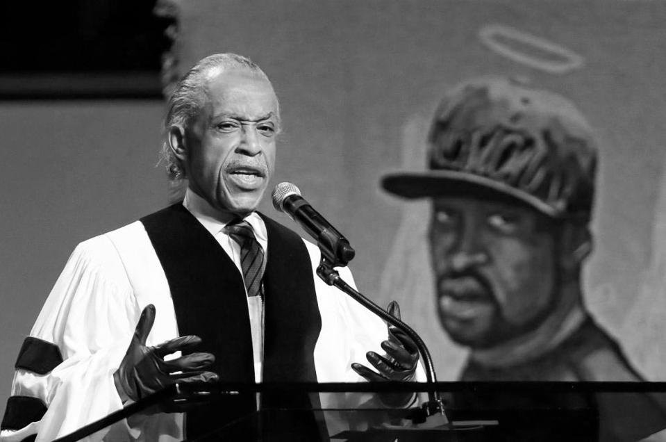 A reverend gives a speech in front of a mural depicting George Floyd with a halo.