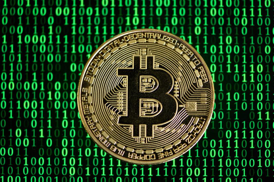 Bitcoin, a cryptocurrency, displayed against a background showing computer code.