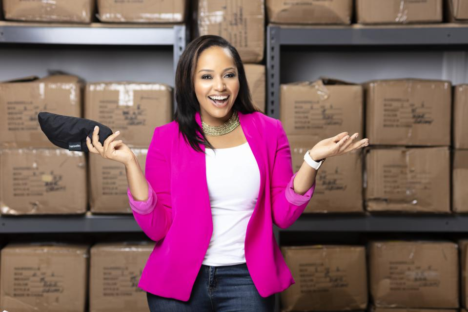 Tracey Pickett in storage room in front of boxes with Hairbrella merchandise