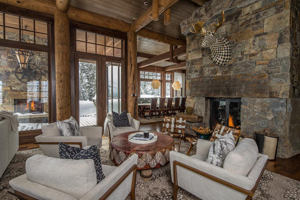 The home features several formal gathering spaces such as the living room and dining room, with doors that open to a covered outdoor dining and deck area.