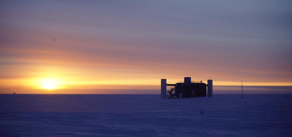 The sun setting behind the IceCube Lab at the South Pole.