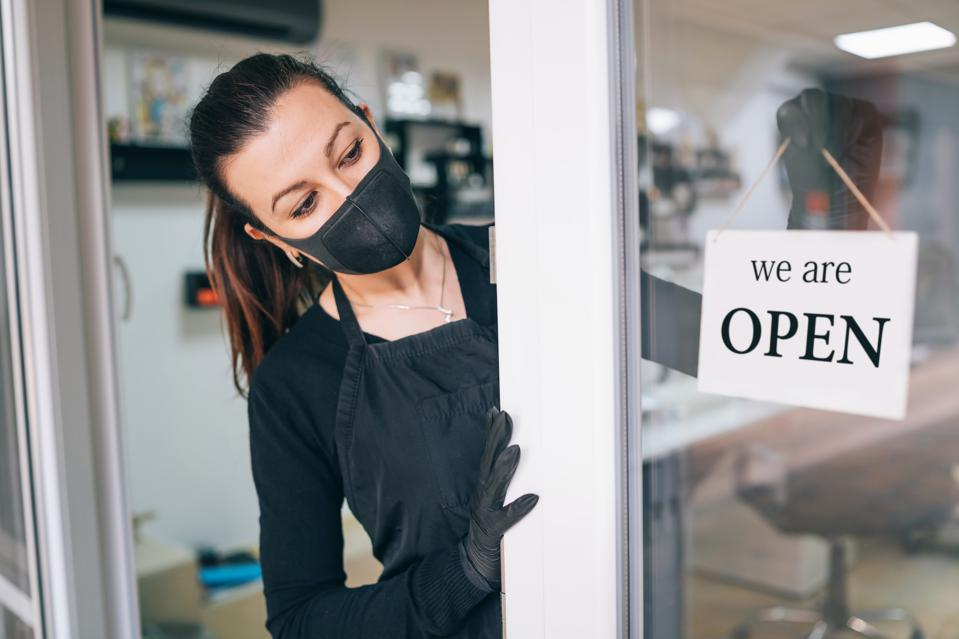 A woman wearing a mask opens the door to her business.