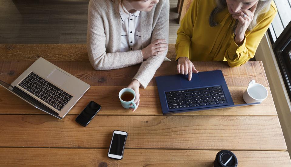 Creative businesswomen having informal meeting in modern open plan office