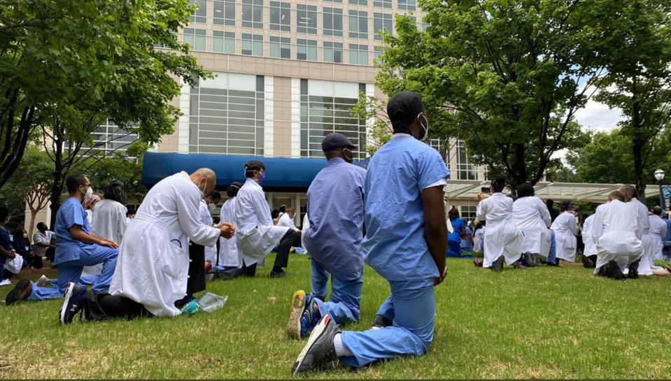 Healthcare workers in scrubs and whitecoats kneel in honor of George Floyd by hospital