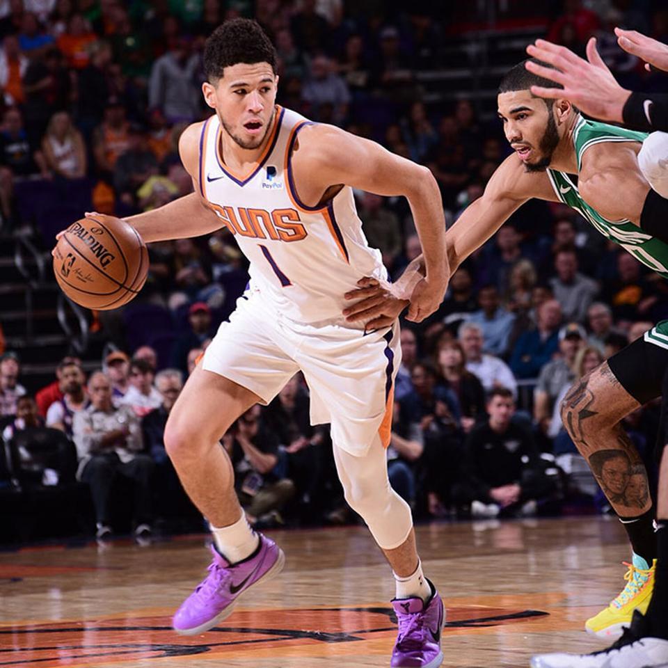 Phoenix Suns guard Devin Booker drives past Boston Celtics forward Jayson Tatum in a game before the NBA suspended the season.