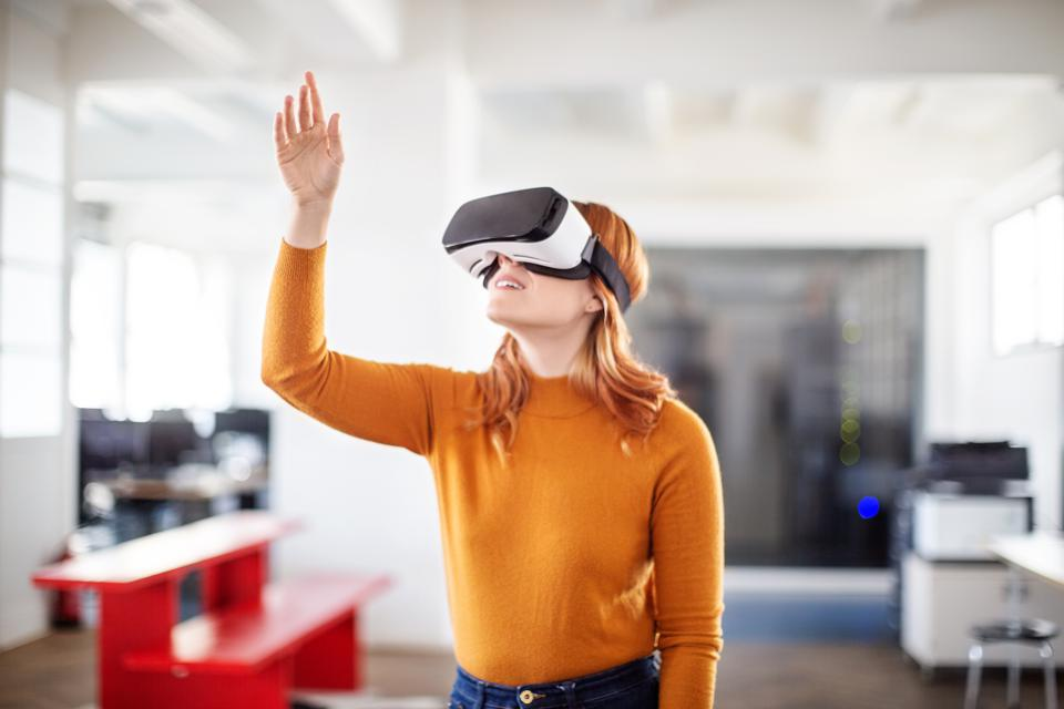 Curious businesswoman using VR goggles