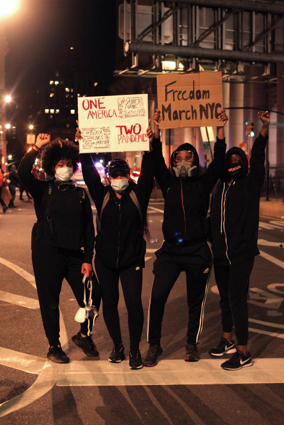 Protesters at Freedom March NYC hold sings in the air and wear masks at night.