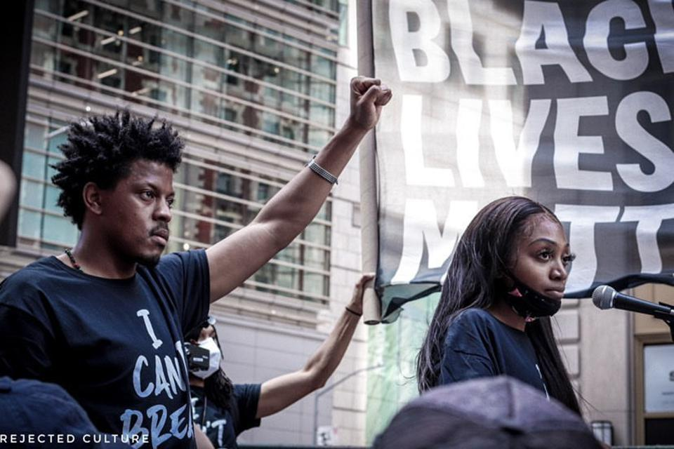 An organizer for Black Lives Matter stands at the microphone. Man has power fist up.