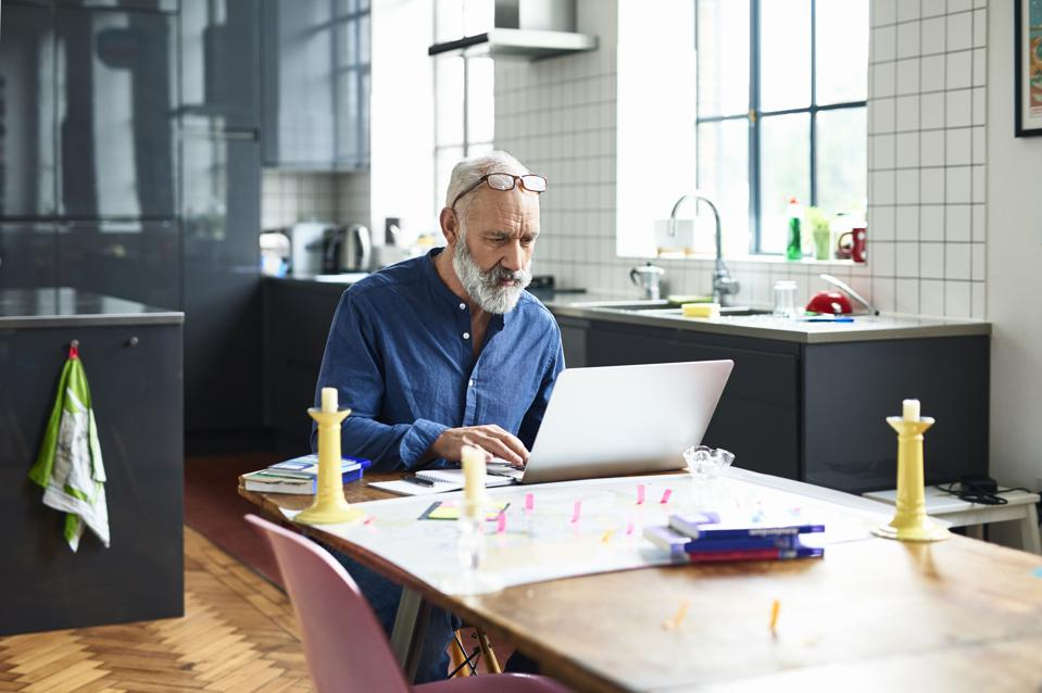 Hipster senior man using laptop with map on table