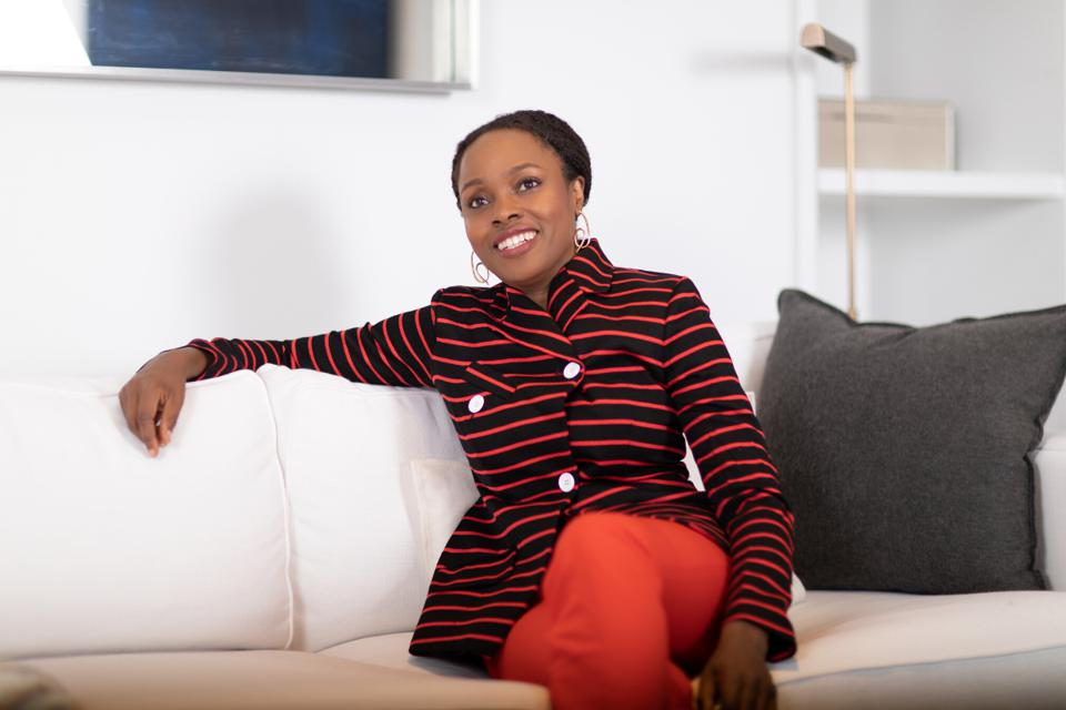 Nichole Campbell sitting on a white couch. How To Express Your Style On Video