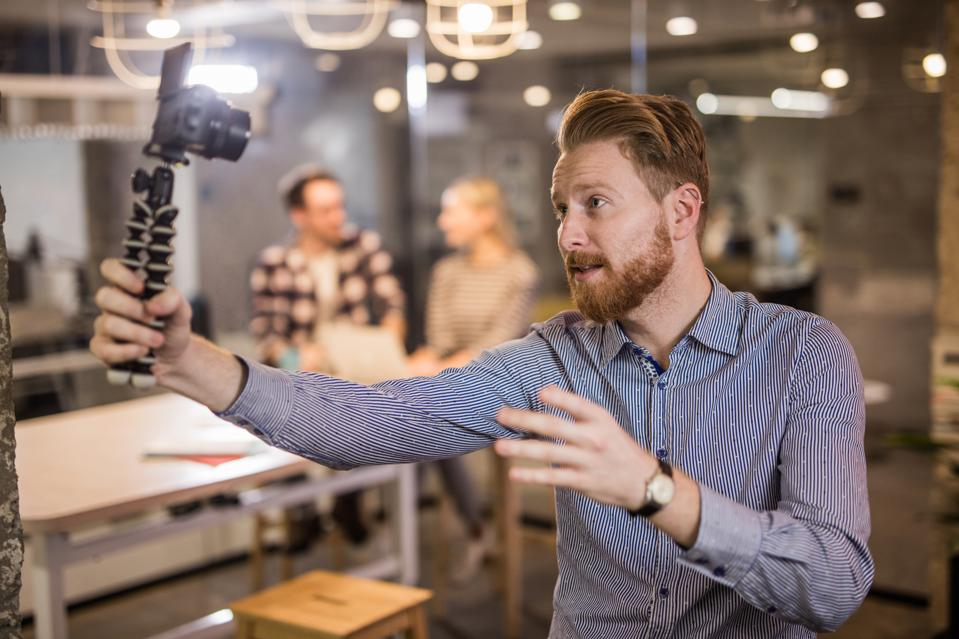 Young redhead businessman vlogging at casual office.