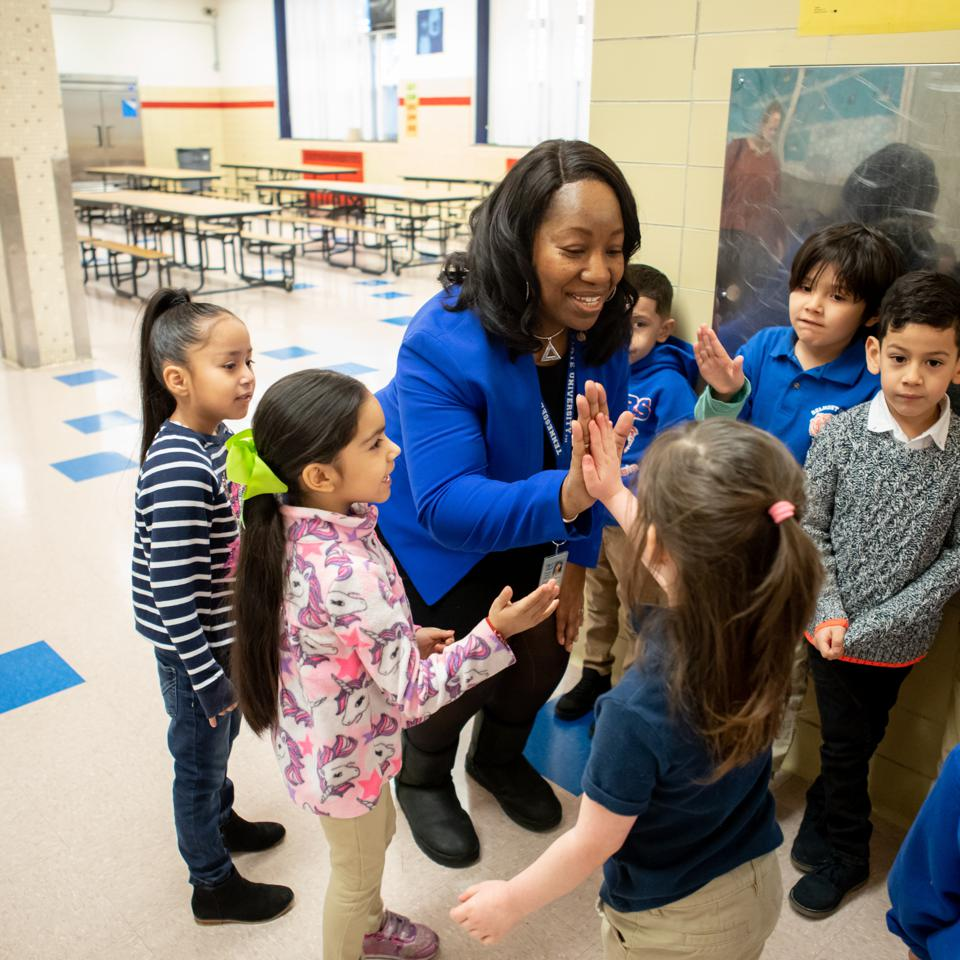 Principal Stacy Stewart warmly greeting kindergarten students at Belmont-Cragin Elementary