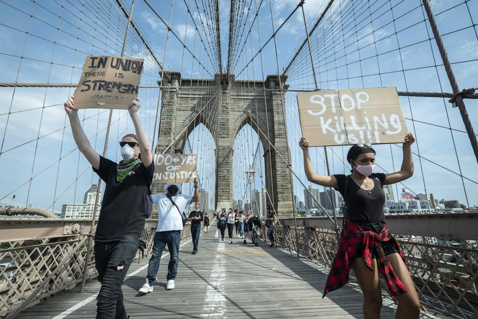 Protestors walk across the Brooklyn Bridge.