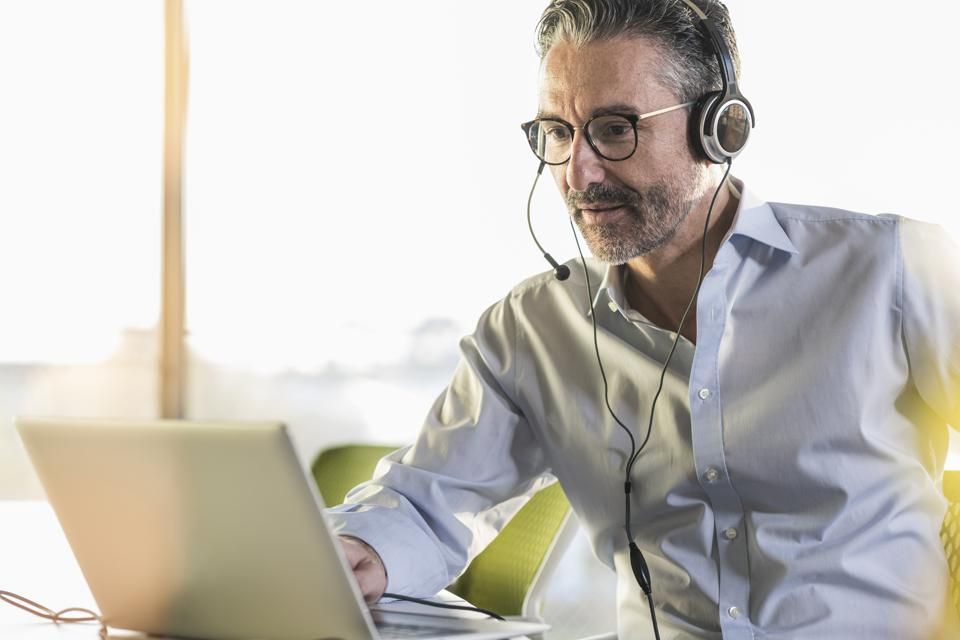Mature businessman wearing headphones using laptop at desk in office