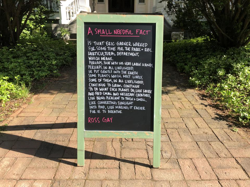 A green sandwich board with a poem.