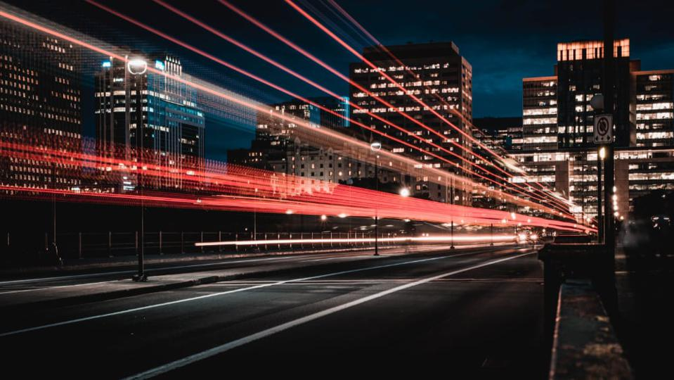 Lights streaking across a city, showing speed and acceleration.