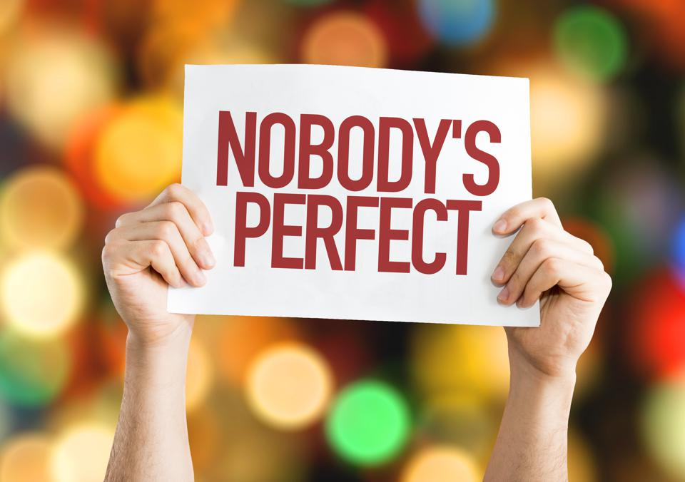 A person holding up a sign that says, ″Nobody's Perfect″