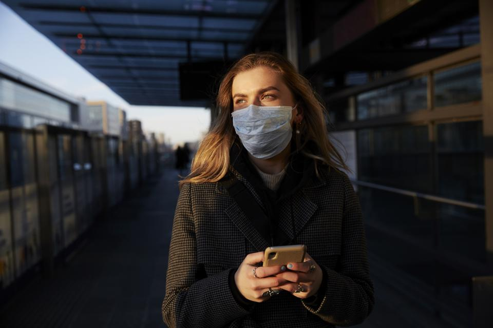 Young woman standing on train station wearing protective mask, using phone