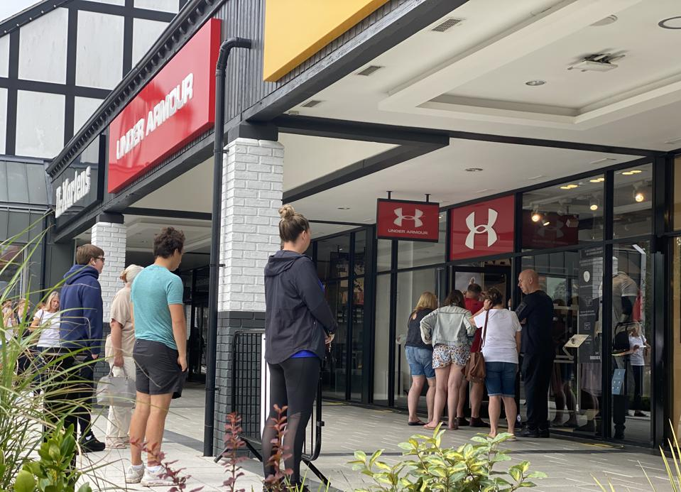 The Under Armour store is pictured from the outside with a queue of shoppers.