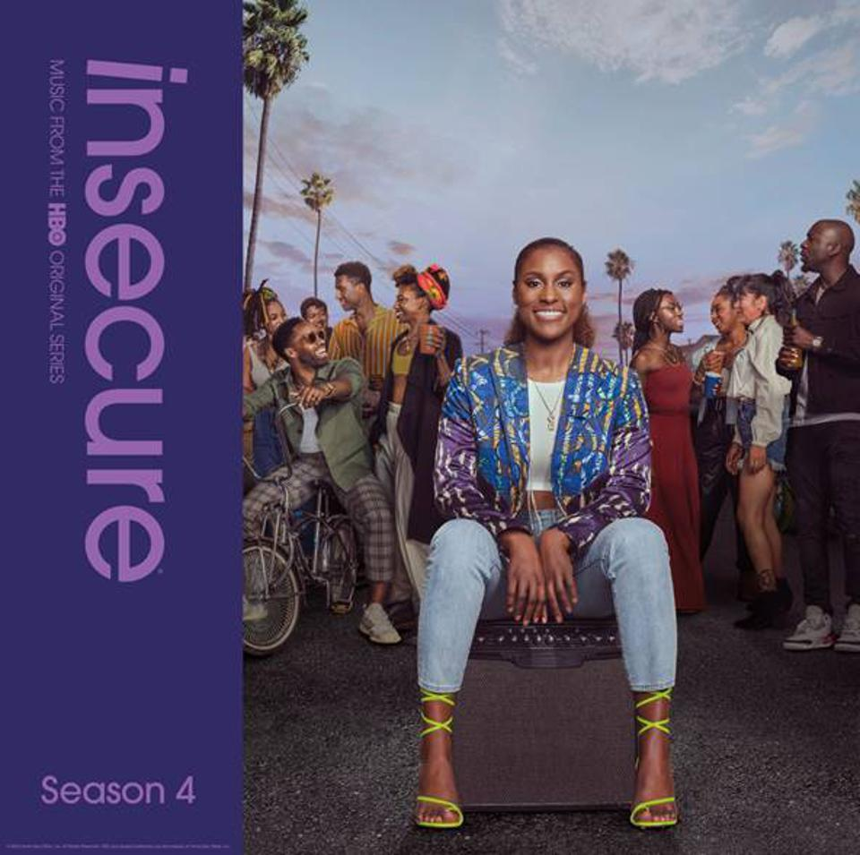 A purple album cover, featuring actress Issa Rae in front of an array of friends and trees