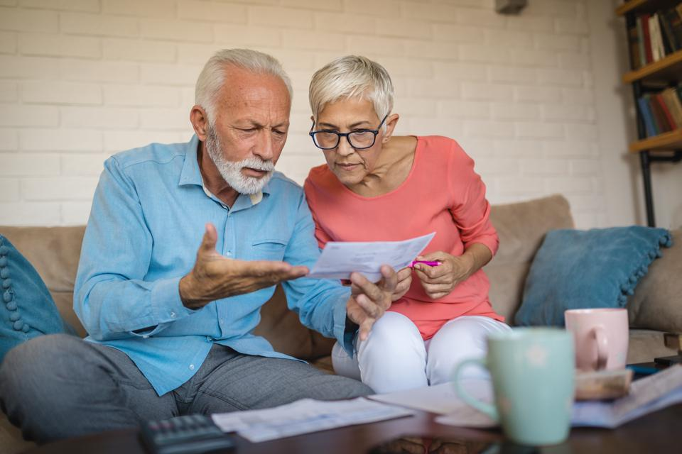 Senior couple in debt calculating bills at home