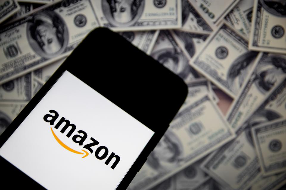 amazon logo on a smartphone with a pile of cash in the background