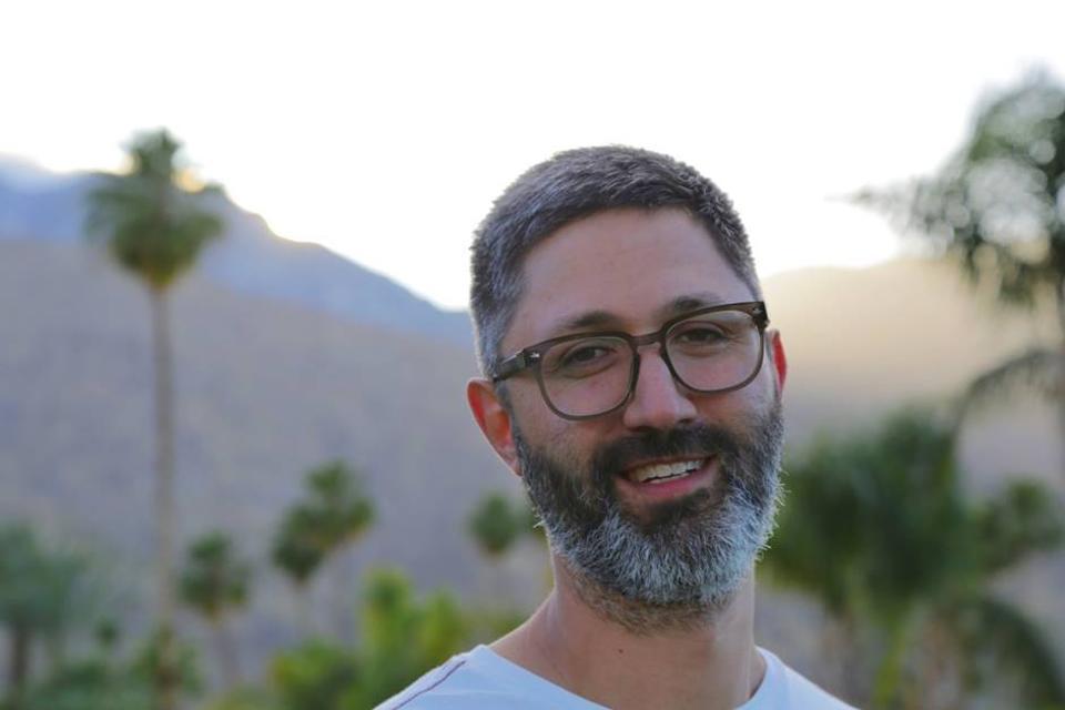 The headshot of Kier Lehman, music supervisor, against a background of palm trees.