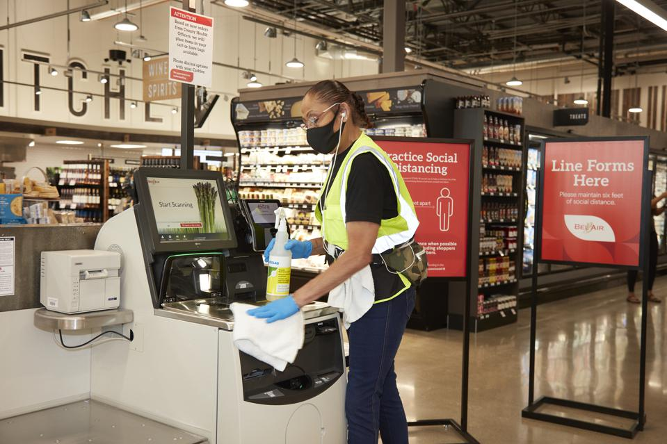 A Raley's team member sanitizes a self-checkout in the new store
