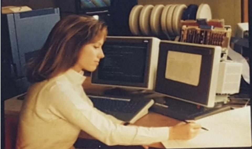 Image of woman coding on computer in 1980s.