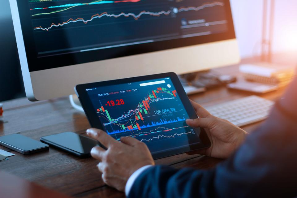 Businessman checking stock market on digital tablet and a desktop computer