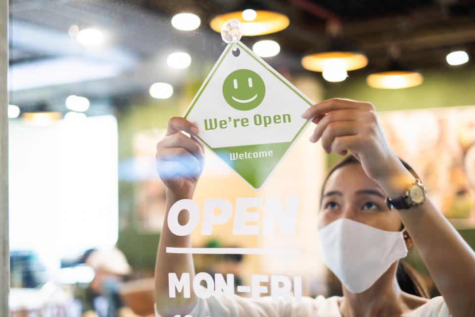 Business owner wear protective face mask ppe hanging open sign at her restaurant