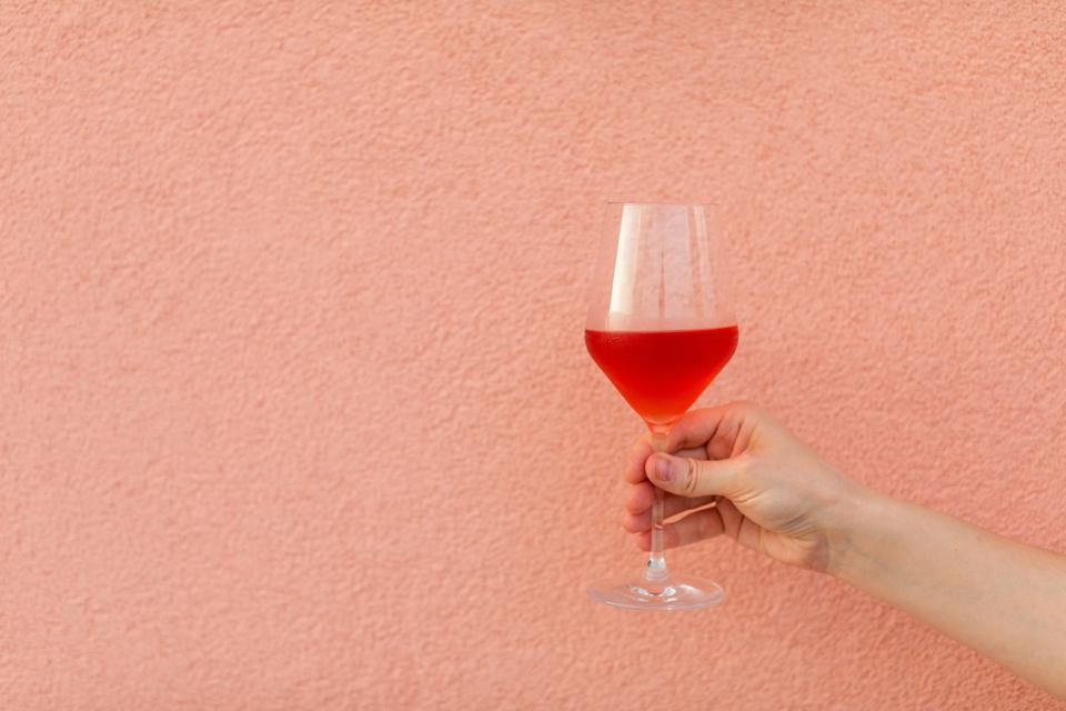A hand holding a glass of rosé wine