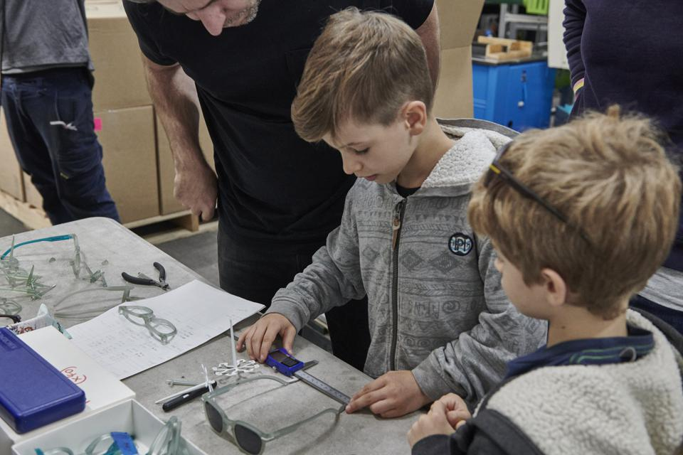A man and his sons looking at glasses at a factory