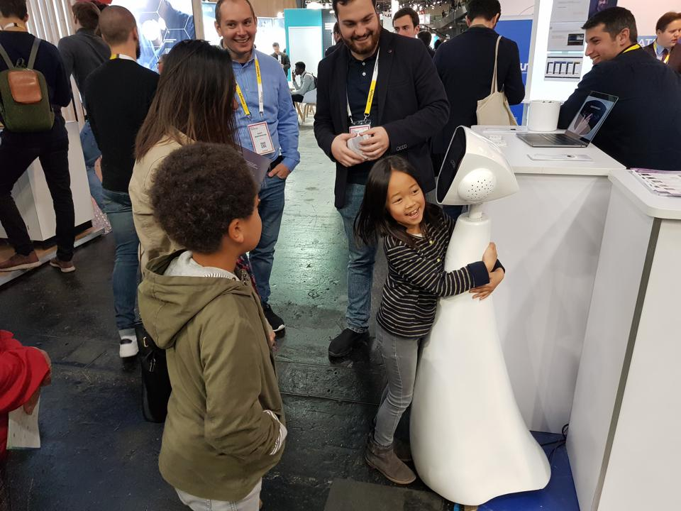 A girl hugs Robin the Robot at an expo in France.